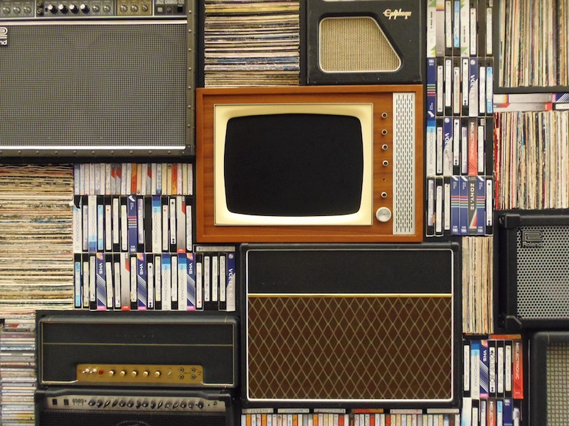 A group of old media types including a CRT television display, stacks of records, and tapes.